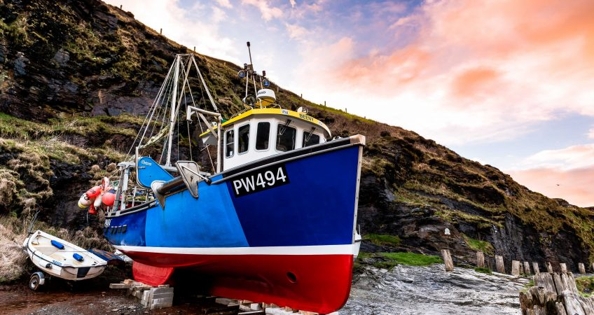A freshly painted fishing vessel rests out of water in the quaint fishing harbour of Boscastle, Cornwall.