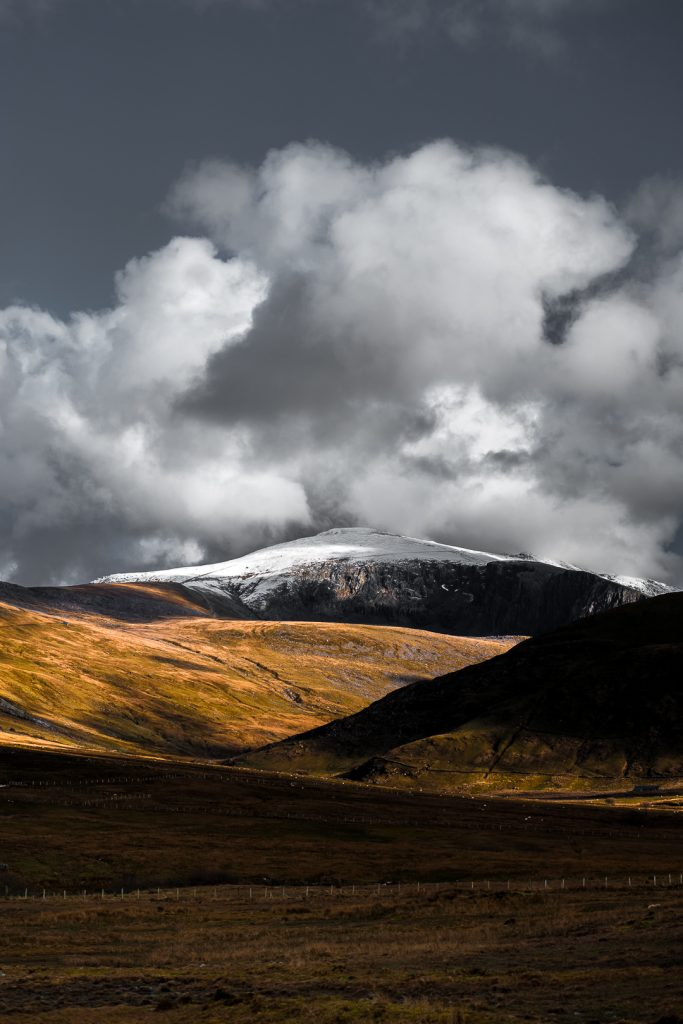 A portrait image of mount snowdon in the winter lightly dusted in snow