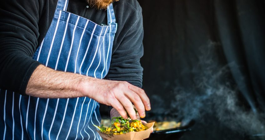 A image of a street food market chef wearing a santa hat prepares a take away meal for a hungry customer