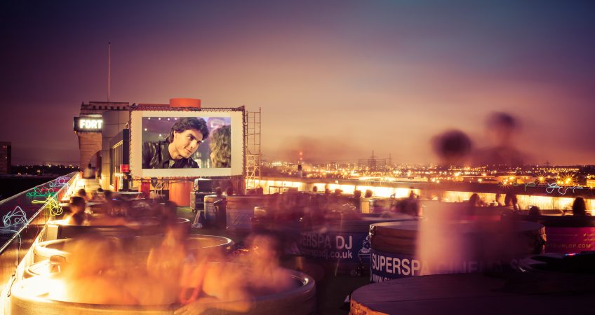 A long exposure image capturing movement of a bustling hot tub party on a roof top in Birmingham at sunset.