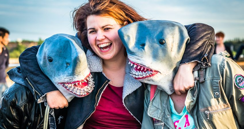 A image of 3 guests at a jaws themed event, the two guests on the left and right are wearing shark masks